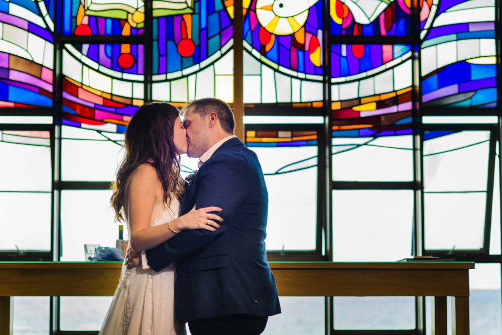 First kiss as husband and wife with stained glass windows in the background
