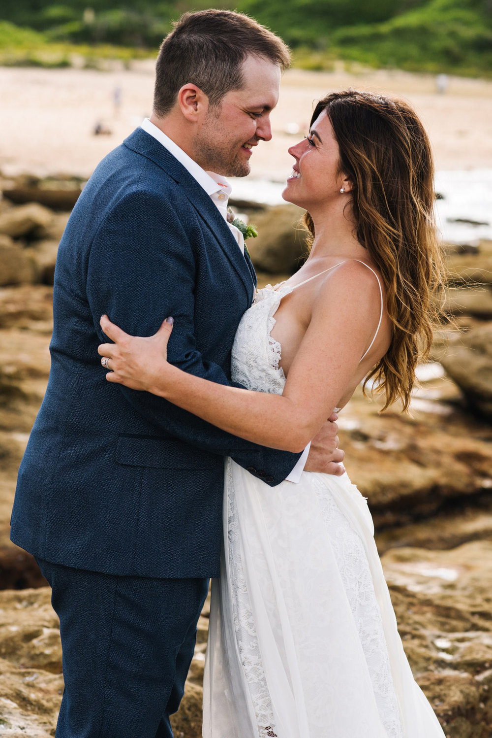 Bride and groom embrace on Sydney beach