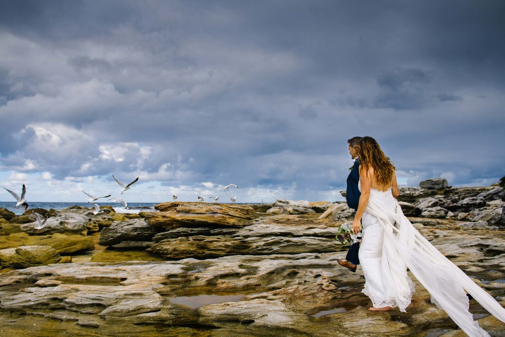 Newlyweds walk along rocky outcrops at Little Bay