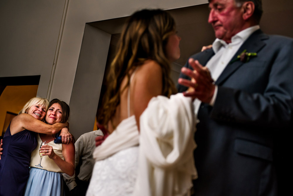 Mother and sister look on during father-daughter dance
