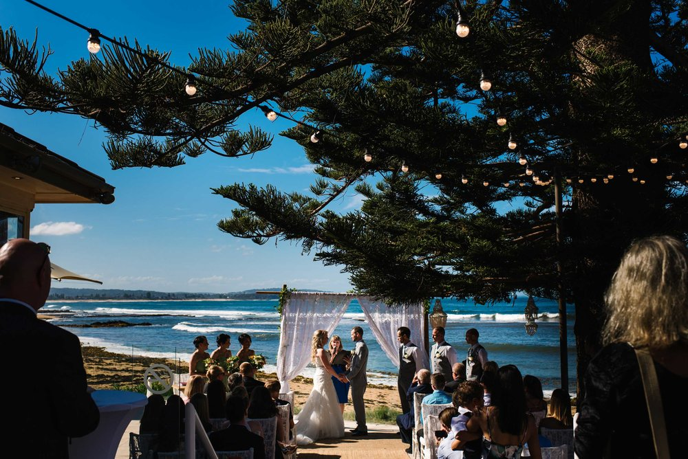 Wedding ceremony at Long Reef Golf Club on patio with beach in the background