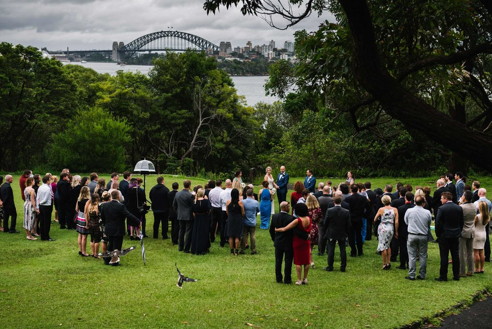 Wedding ceremony on lawn in front of Athol House, Mosman, with city and harbour in background