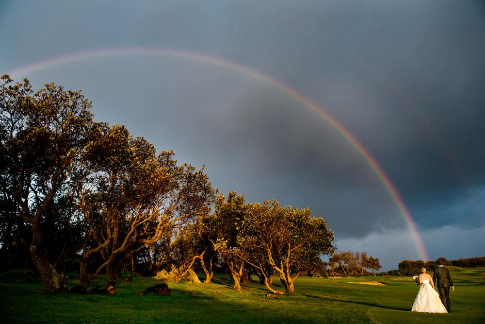 Bride and groom under a rainbow on Long Reef Golf course