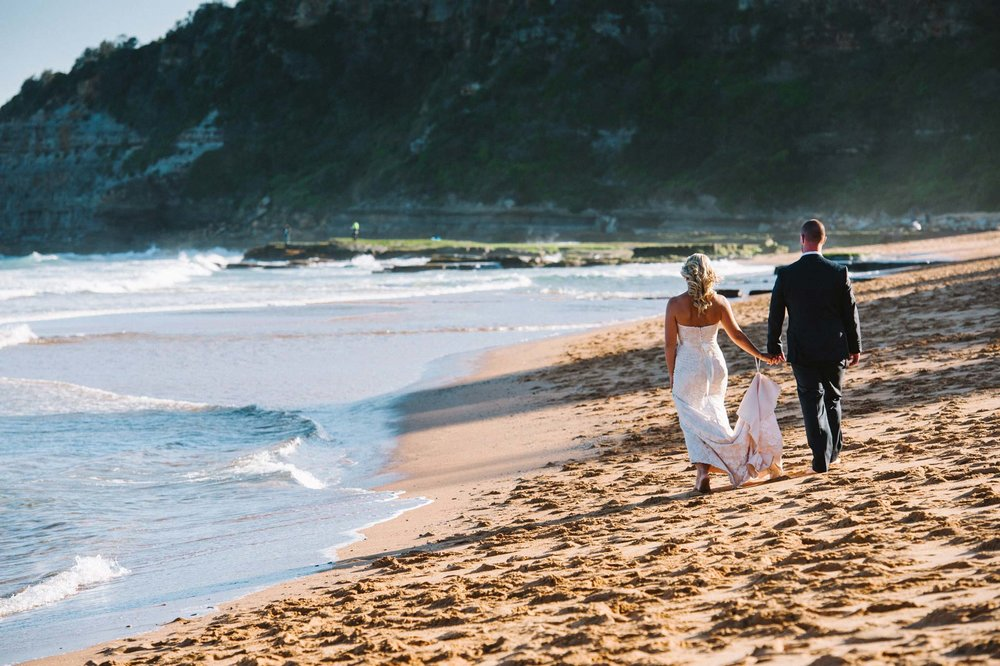 Newlyweds walking along beach at Turimetta