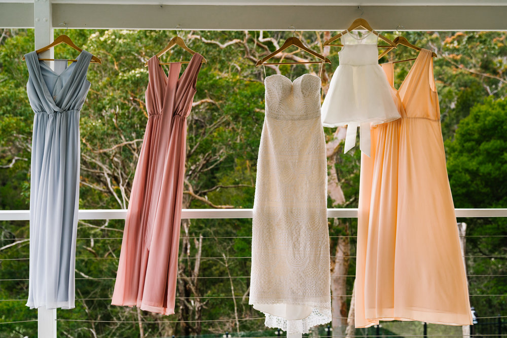 Beachy bridesmaids gowns hanging in front of bushland backdrop