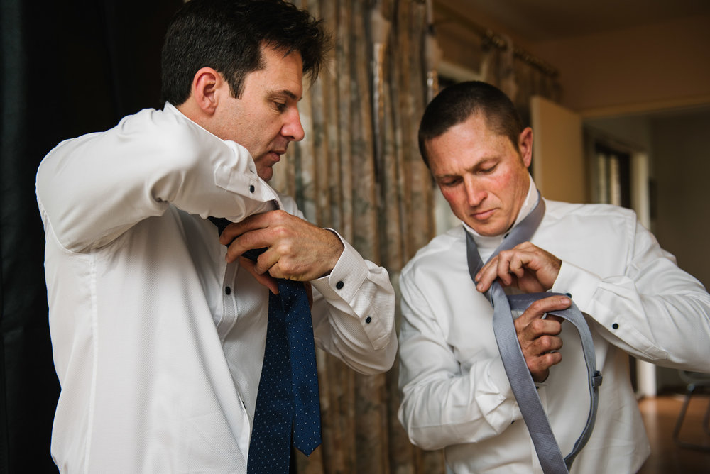 Groom and groomsmen tying ties