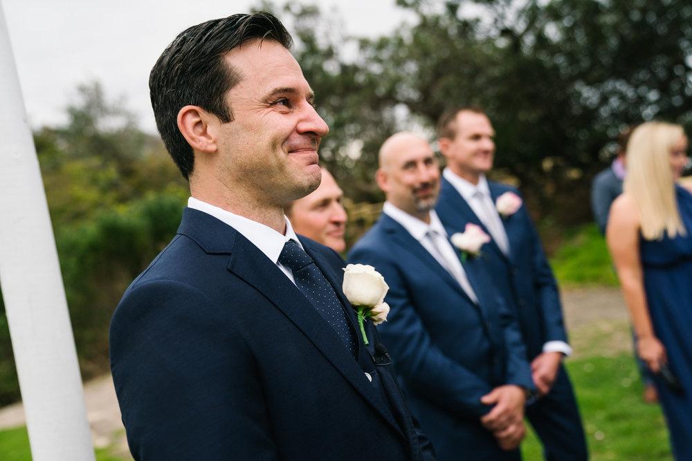 Groom tearing up as bride walks down the aisle toward him at Shelly Beach wedding