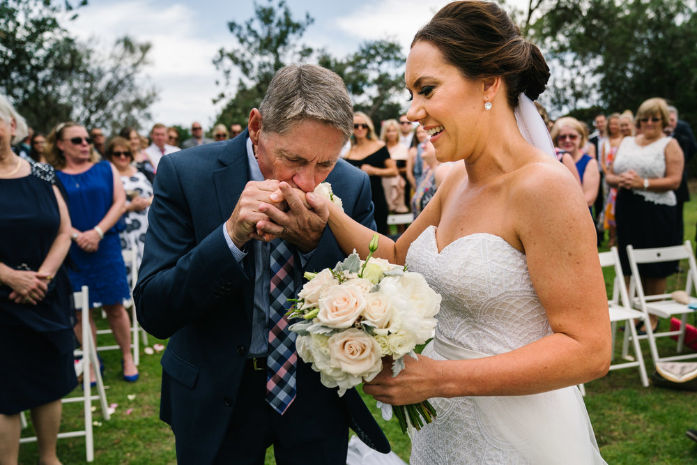 Father kissing bride's hand at the end of the aisle
