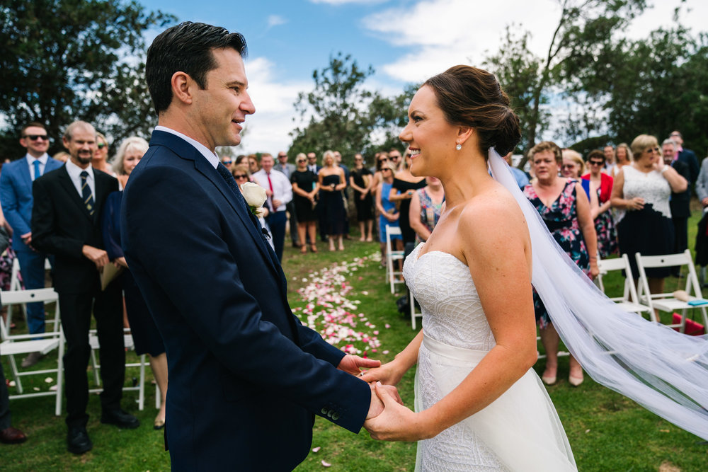 Bride and groom smiling while guests look on at their Shelly Beach wedding