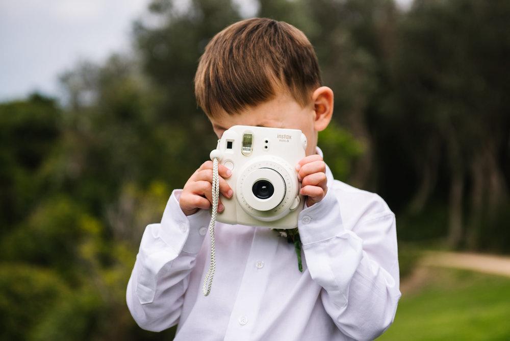 Ringbearer taking photo with an instax polaroid camera