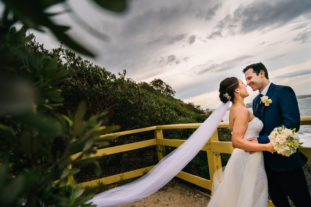 Newlyweds embracing with view of ocean in the backdrop