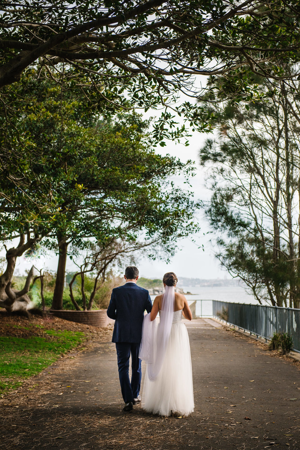 Bride and groom walking down aisle of trees at Little Manly