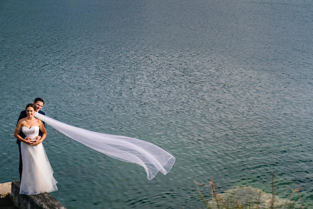 Bride's veil flowing in the wind with ocean in the backdrop