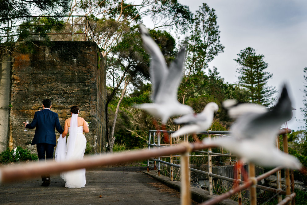 Bride and groom walking with birds flying in the foreground