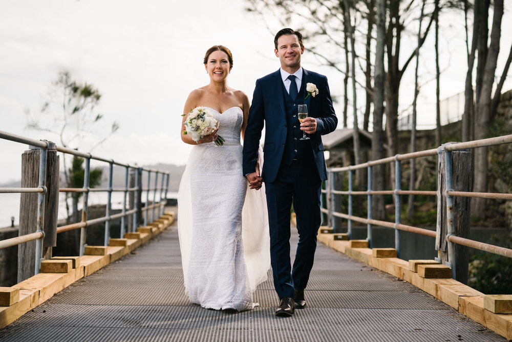 Newlyweds walking over bridge at Little Manly Beach