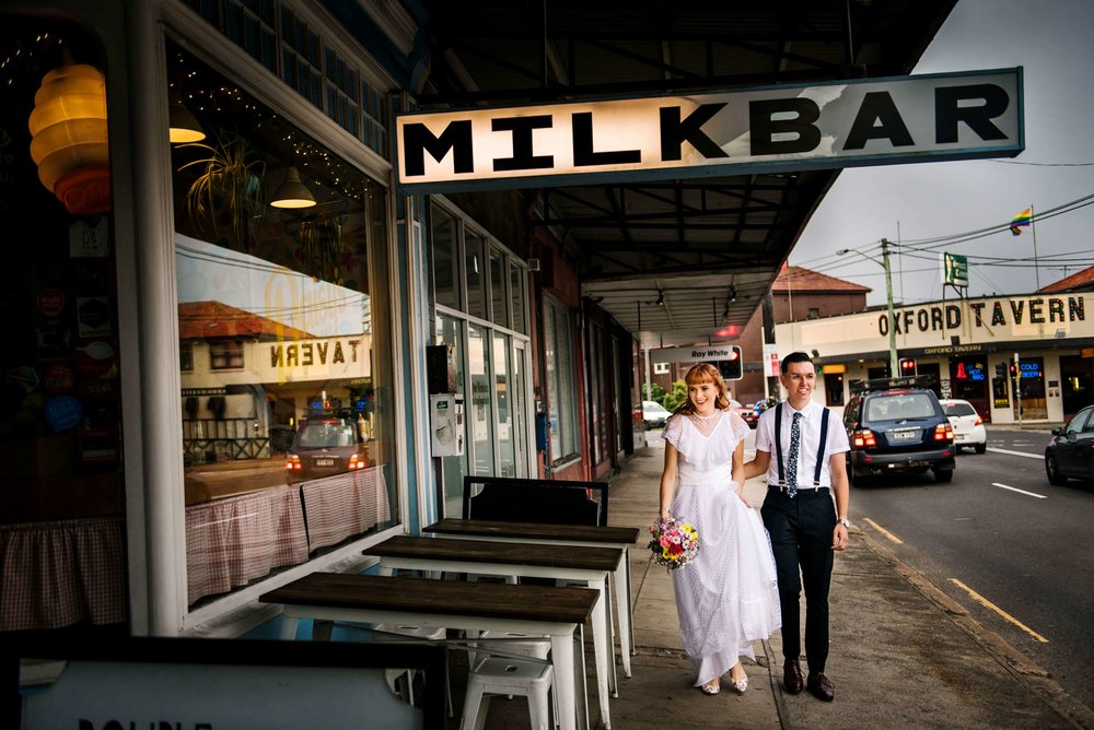 Newlyweds walking in front of Daisy's Milk Bar Petersham