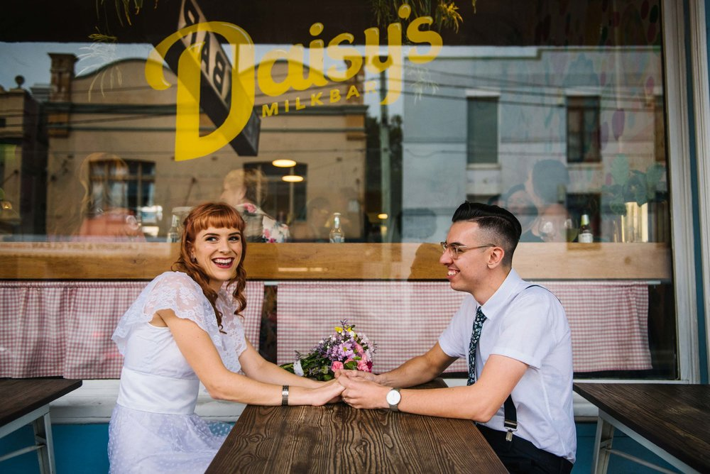 Couple holding hands in front of Daisy's Milk bar in Petersham NSW