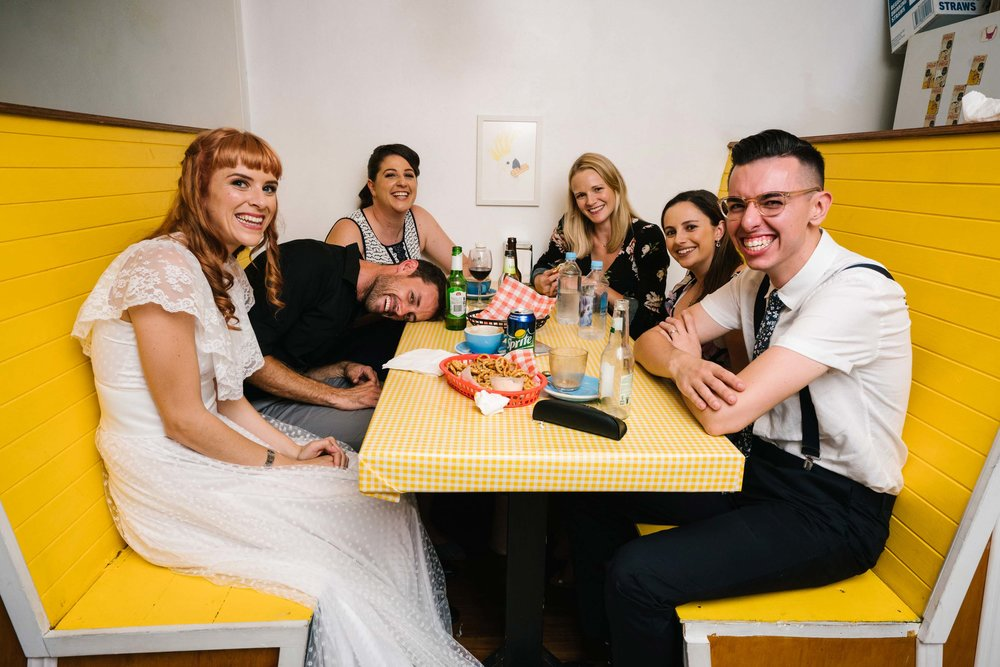 Newlyweds with guests in booth at retro wedding reception