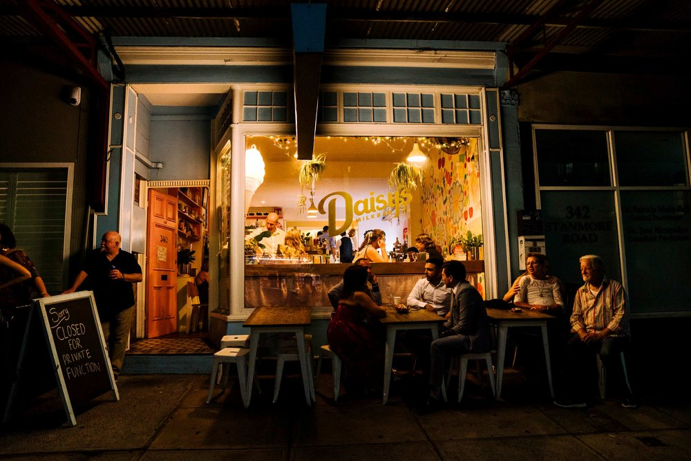 View of Daisy's Milk bar at night with wedding guests out front