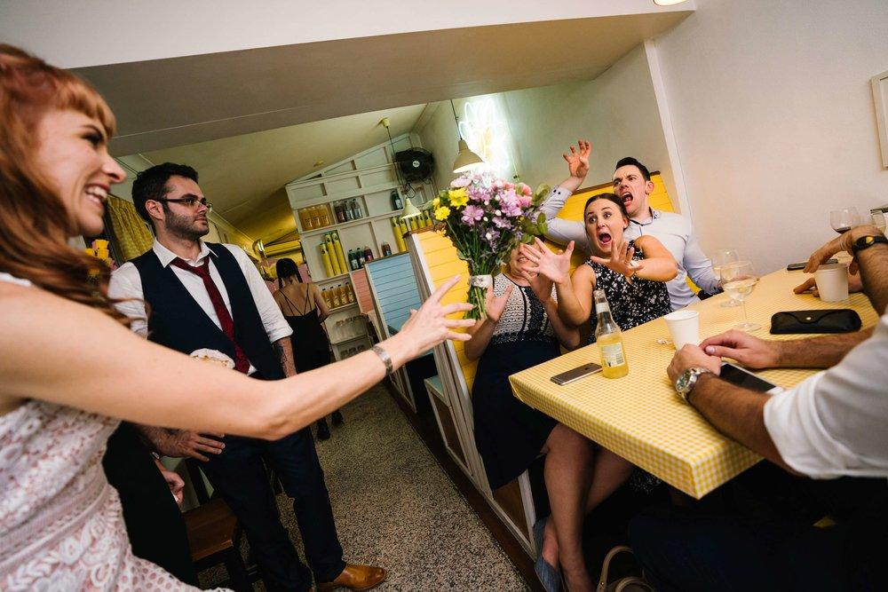 Bouquet toss at quirky milk bar wedding reception