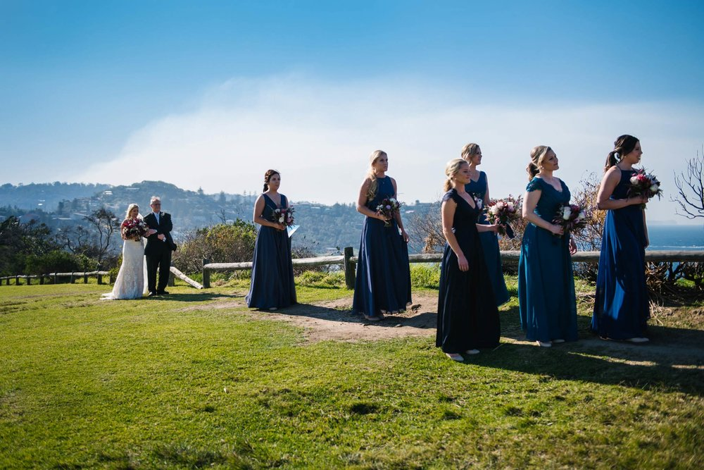 Bride, father and bridal party approaching the ceremony on Mona Vale headland