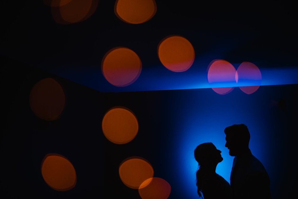 Silhouette of couple against a blue backdrop and golden lights in the background