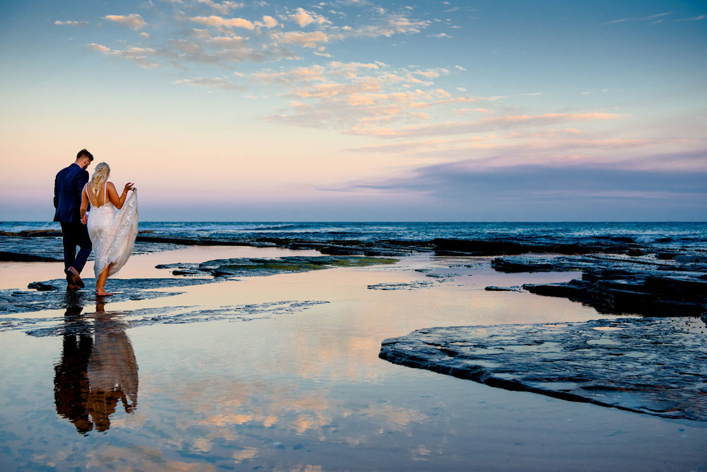 Reflection of newlyweds on the water at Narrabeen pools at sunset