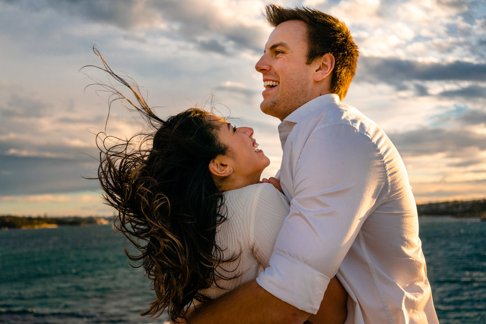Couple laugh as wind blows their hair around during engagement session at Watsons Bay