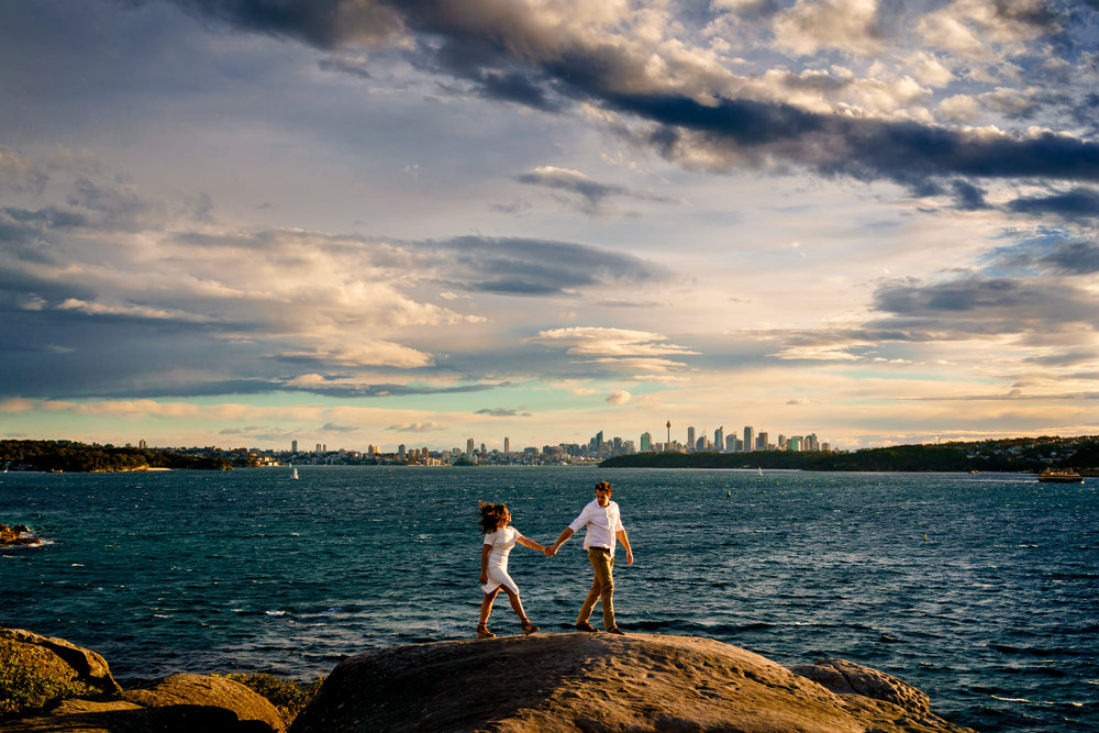 Engaged couple walk along rock cliffs with Sydney city and the harbour in the background in Watsons Bay NSW