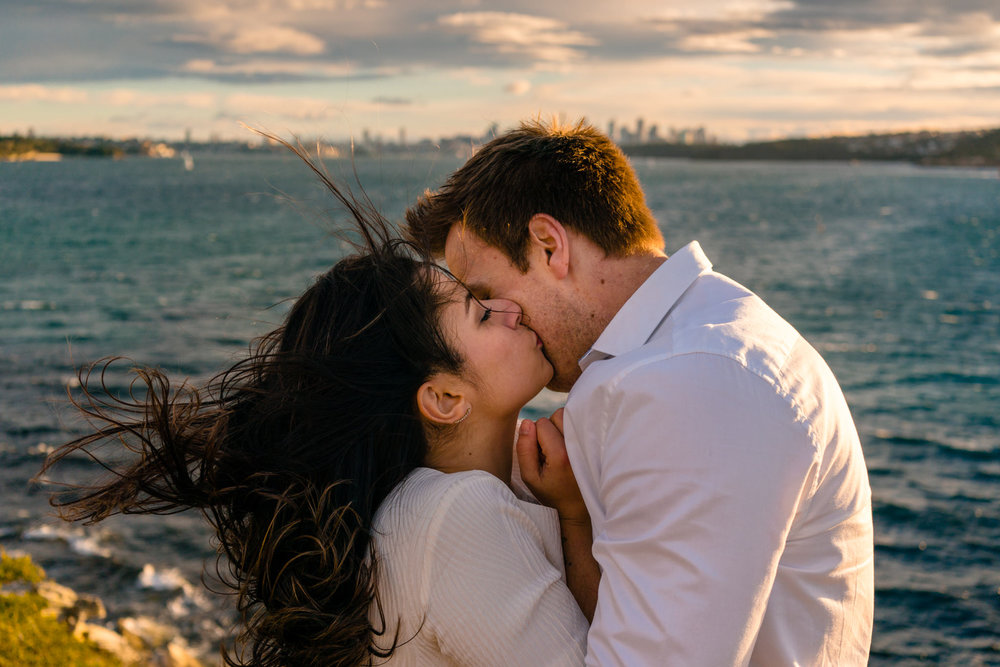 Couple kiss on windy cliff at Watsons Bay