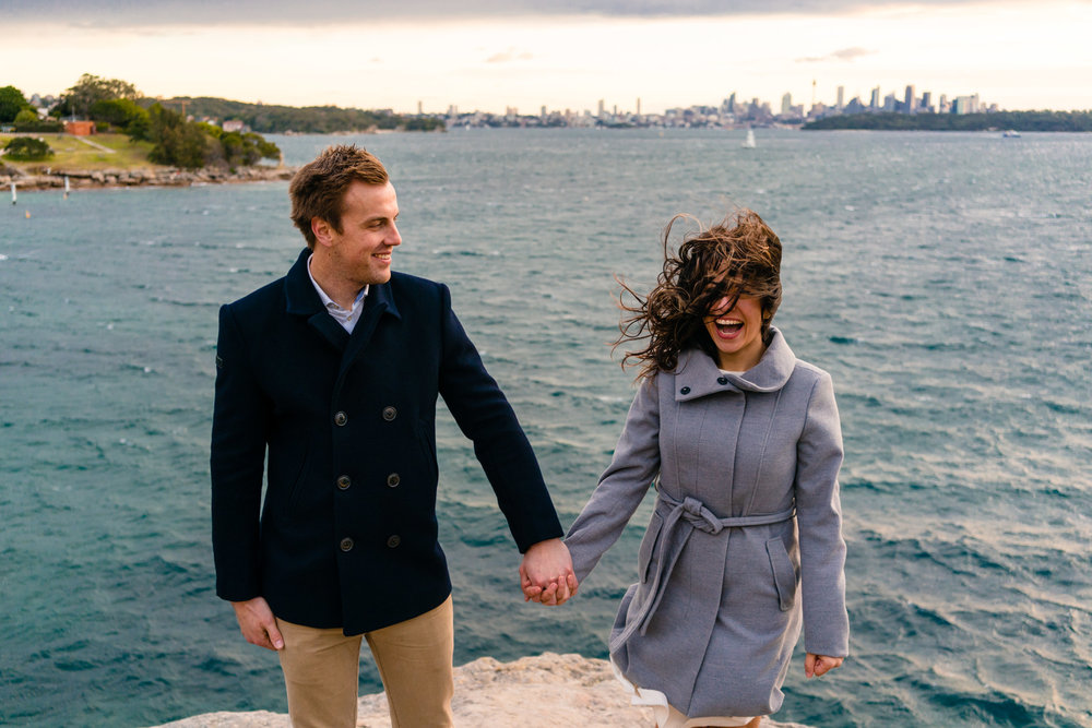 Couple laughing as wind blows during ocean front engagement session