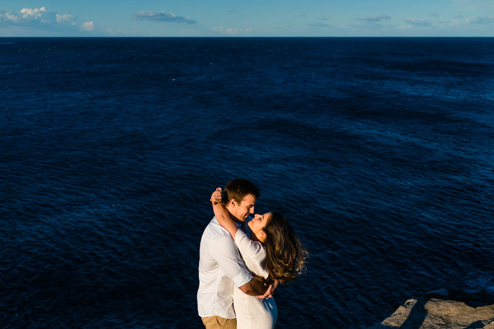 Newly engaged couple kiss on cliff top with harbour in the backdrop