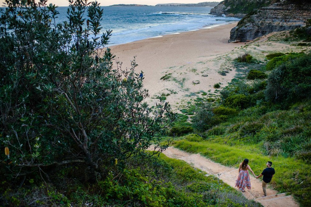 Couple walking down stairs to the beach in Sydney's Northern Beaches