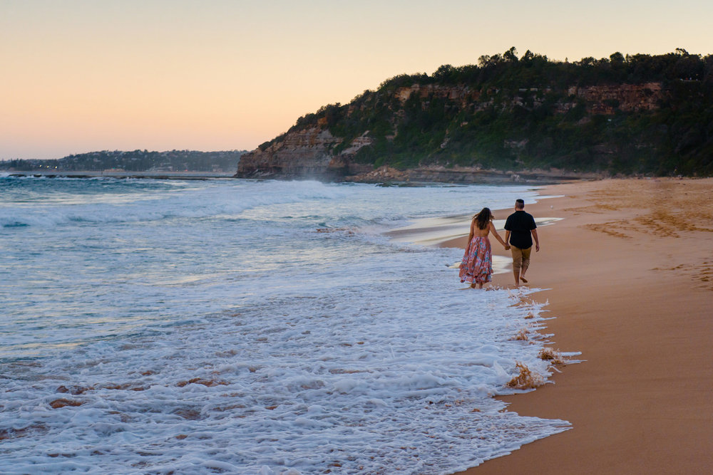 Couple walking along the beach during Northern Beaches engagement session