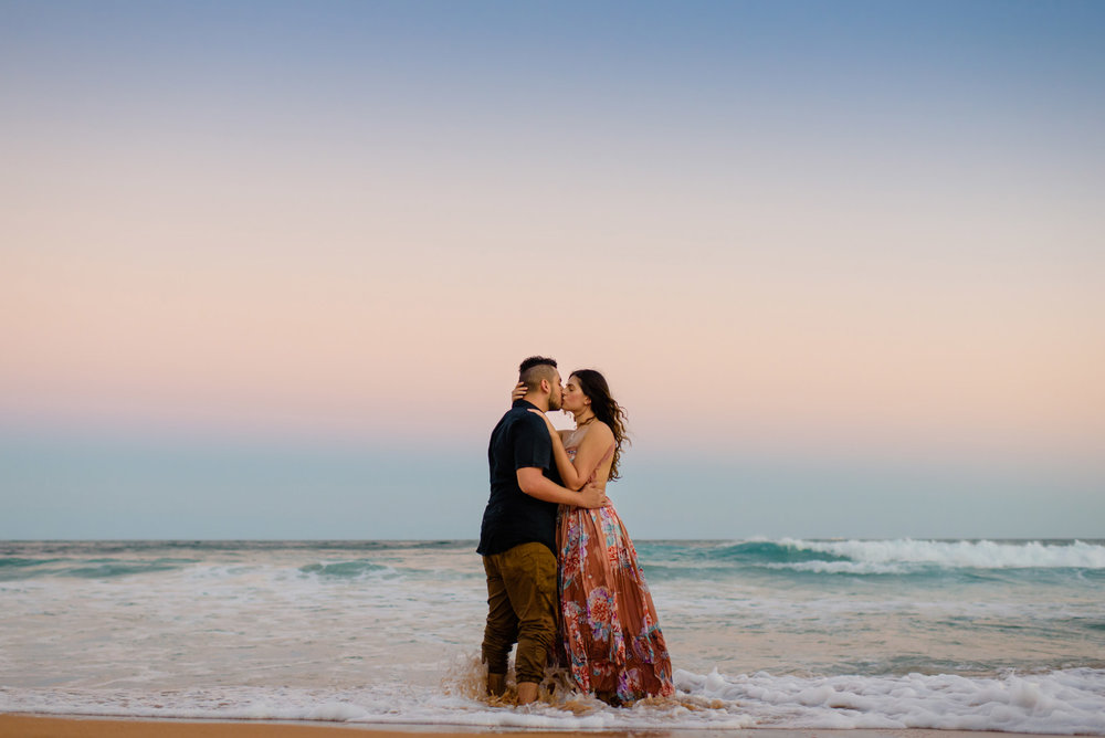 Engaged couple kissing in with their feet in the ocean and sunset colours in the sky behind them