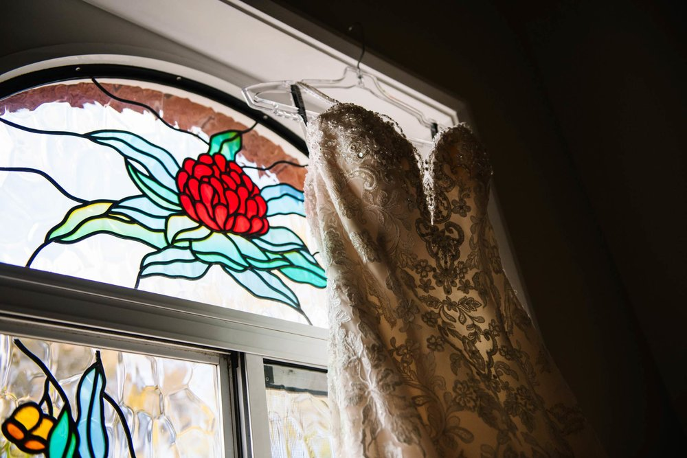 Bridal gown hangs in front of stained glass window