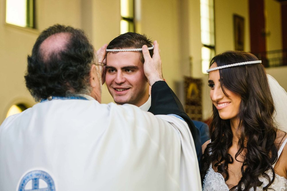 Priest puts crown on grooms head during Greek orthodox wedding ceremony in Sydney