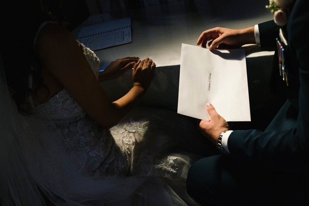Newlyweds holding their marriage certificate