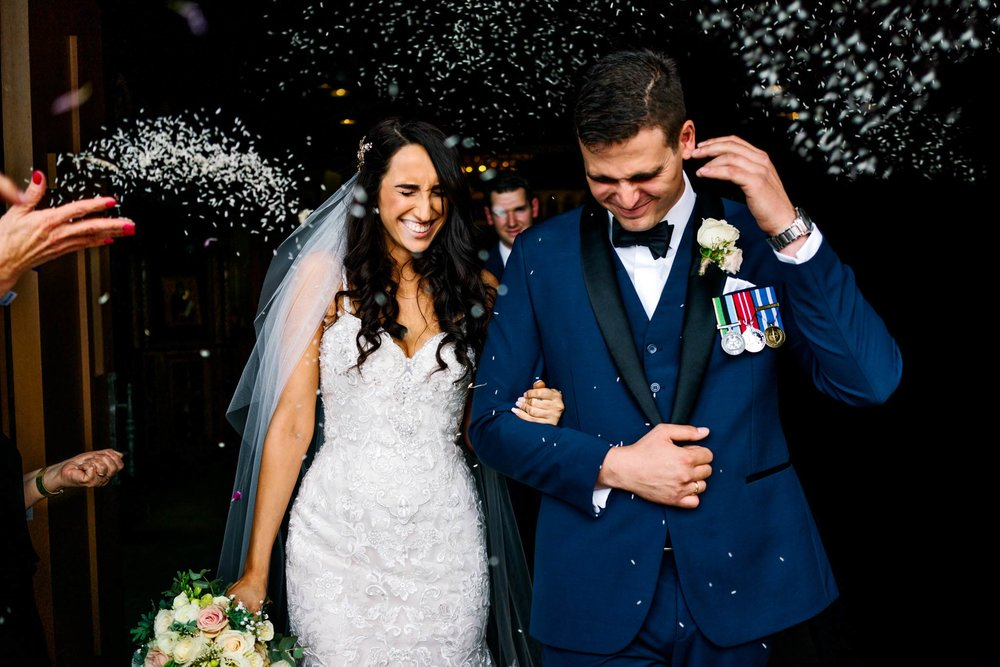 Bride and groom laugh as guests throw rice on them as they exit the church