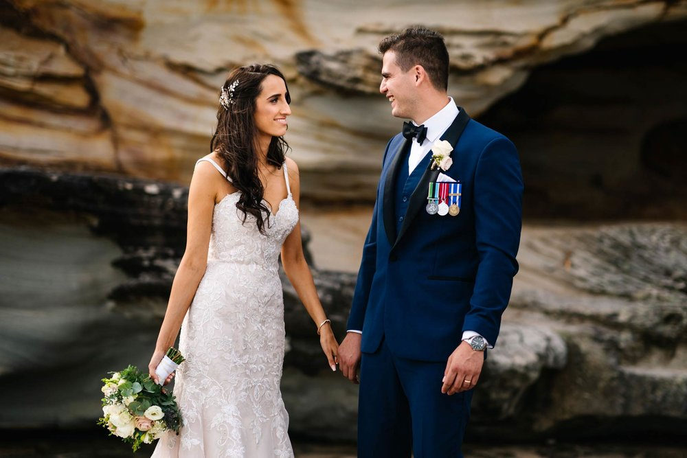 Newlyweds laughing and holding hands during bridal portraits on the Northern Beaches