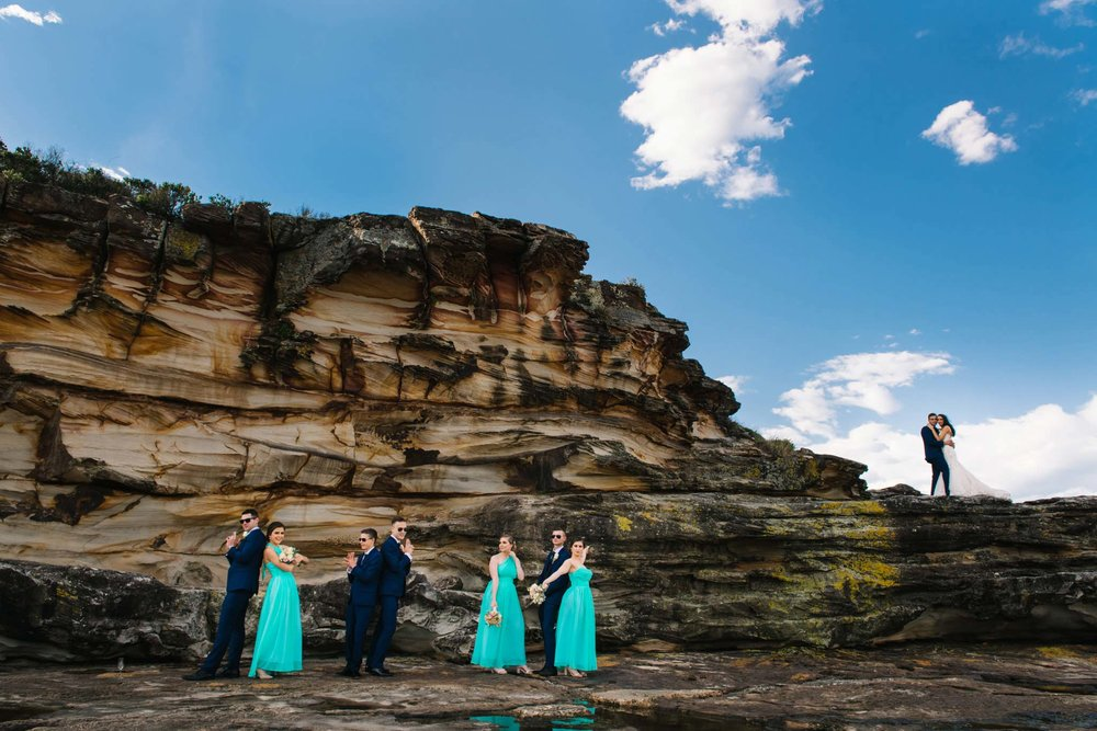 Bridal party in front of a sandstone cliff with newlyweds in the backdrop at Freshwater headland