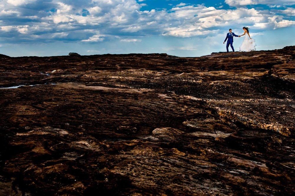 Newlyweds walking along moon-like rocks at Freshwater beach