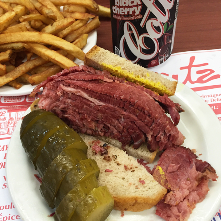 Schwartz's Deli - There was obviously a bit of a wait when I got here, but well worth the wait. Every bite was amazing even though I just possibly could not finish this sandwich! As told by the waiters, one must get the side of pickles and fries with the black cherry soda with this dish: Smoked Meat Sandwich!