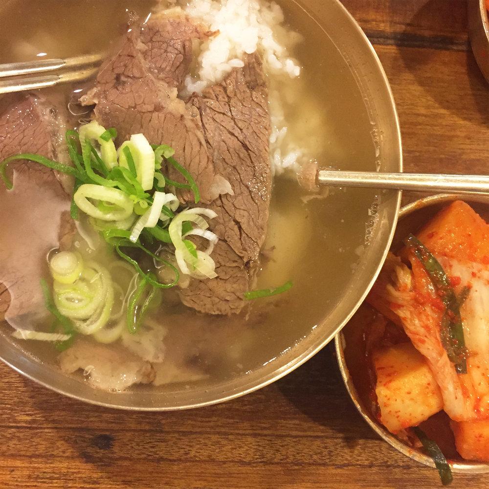 하동관 (Hadongkwan) - This particular restaurant might possibly be one of my favorite places in Korea. It's a place that my dad has taken me to try because I was craving some classic 곰탕 (Oxtail Soup).Here at 하동관 (Hadongkwan), they specialize in these Oxtail Soups (for over 70 years!)and surely, you can taste the best of its kind.The soup is perfect for a sunny day in the Summer when you want to beat out the heat with heat. It is also perfect for when you need that pick-me-up while you're sick in the the coldest of Winters.Photo of 곰탕 (Oxtail Soup) + 깍두기 (Radish Kimchi)