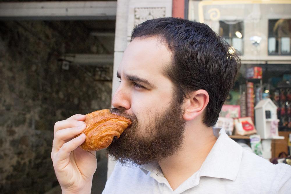 Mr. Burger eats a croissant
