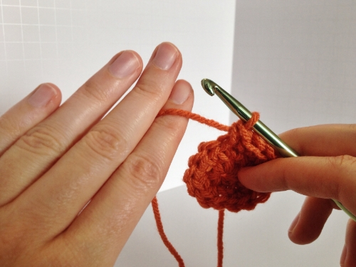 Step 1: Pinch the long end of the yarn between your middle and index fingers.