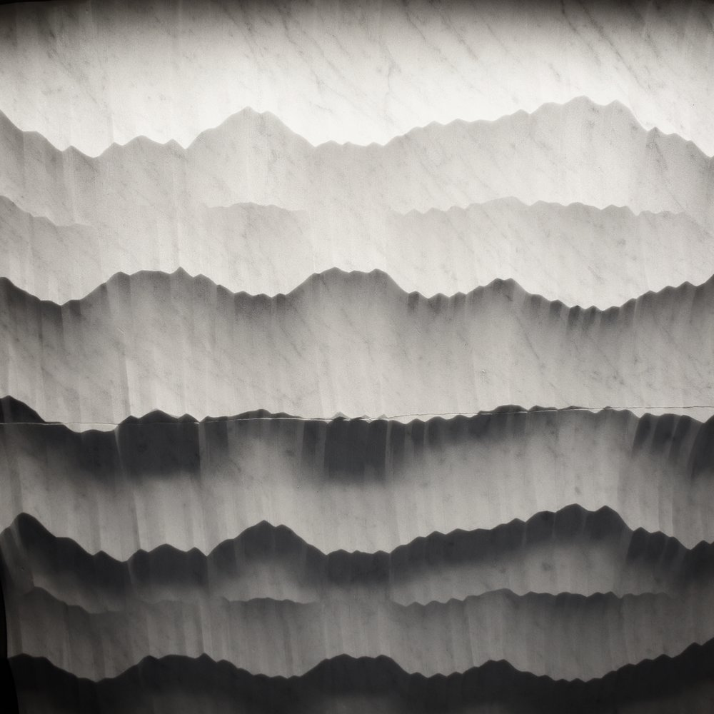 Machined, but random texture creates shadows that reveal a mountain landscape. Hedonism collection by Petra Antiqua