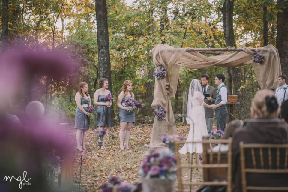 MGB Photo .  Meagan + Alex 's burlap altar with purple floral arrangements against the fall leaves... definitely one of my favorite fall wedding details ever!