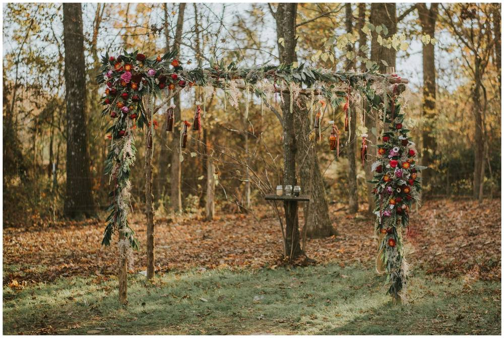 B.Matthews Creative , from  Emaly + Thomas ' wedding. This bohemian altar included amazing florals and hanging bottles... It was unique and gorgeous!