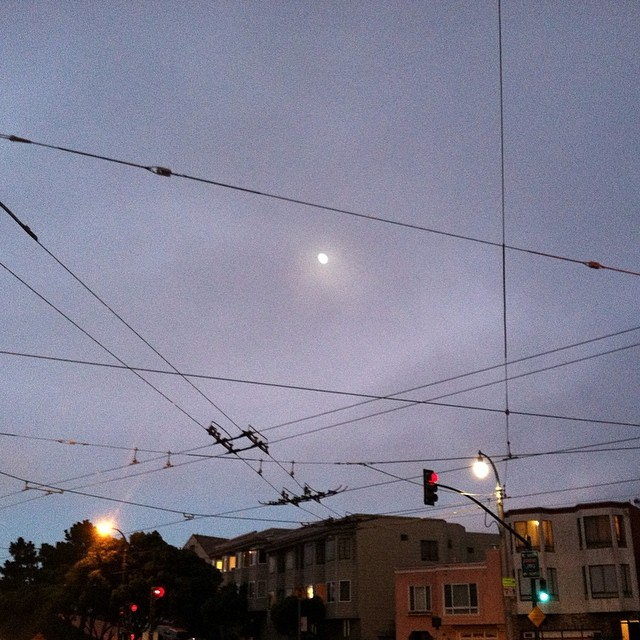 Looking at the moon between the wires. Lights imitate beauty, wake,  inspired.